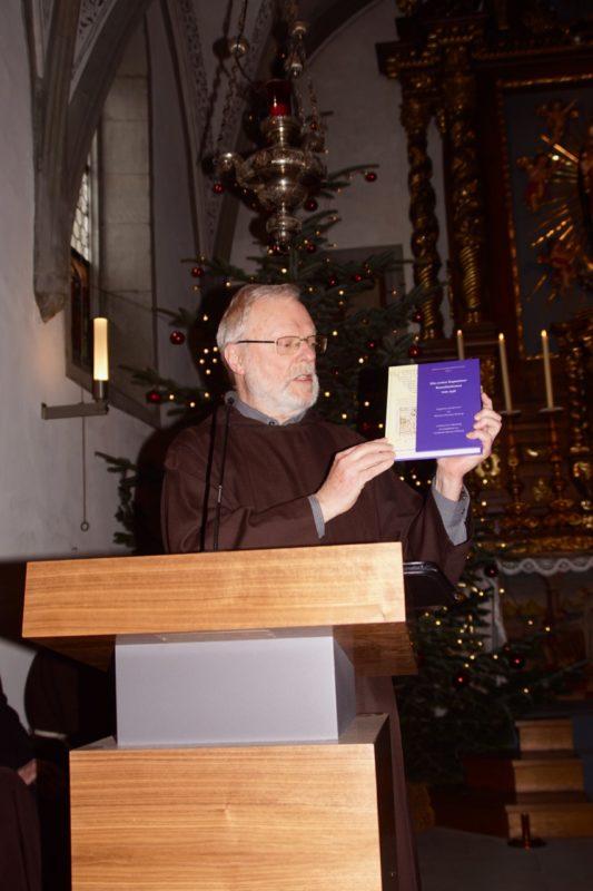 Br. Leonard Lehmann präsentiert das neueste Buch des Gefeierten: die Übersetzung und Kommentierung der Ordensatzungen von 1536 (Bild: Br. Karl Flury)