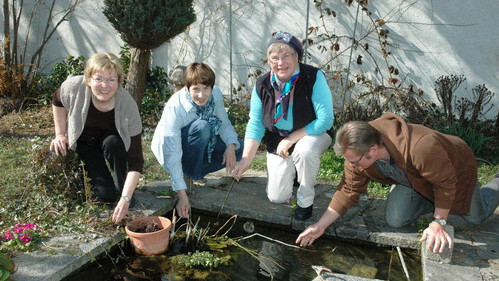 Der kleine Teich wird für seine Glanzrolle hergerichtet. Bruder Paul Mathis mit Gerda Köppel, Brigitte Schönenberger und Marianne Truniger (von rechts) | © Bea Oesch